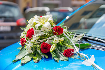 Bunch of wedding flowers at the front of a blue car
