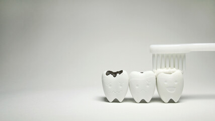 Toothbrush with Toothpaste on Teeth model in happy emotion and Decayed Tooth , if brush teeth will good healthy