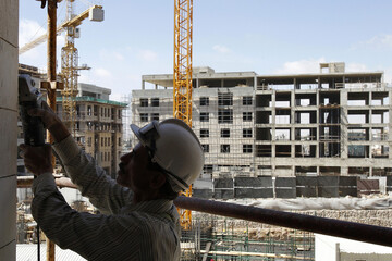 Construction worker builds stones at the site of the Abdali Project in Amman