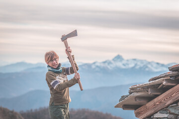 Angry woman holding an axe. Scenic background with mountain peaks, misty valley and moody sky, on the Alps.