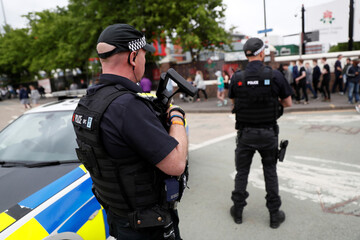 Armed policemen are seen outside the Lancashire County Cricket Club, Emirates Old Trafford, in Manchester, Britain