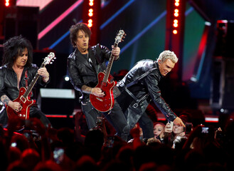 Billy Idol (R) performs with members of his band during the iHeartRadio Music Festival at The T-Mobile Arena in Las Vegas