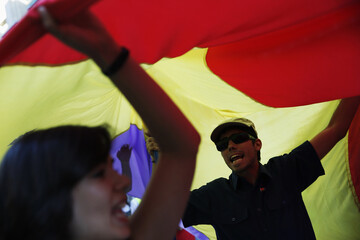 People shout slogans underneath Spanish Republic flag as they march during anti-monarchy demonstration in Madrid