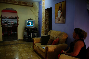 Mariza Betancourt, who runs a small hostel in downtown Havana, watches the inauguration ceremonies to swear in U.S. President Donald Trump on television in Havana, Cuba