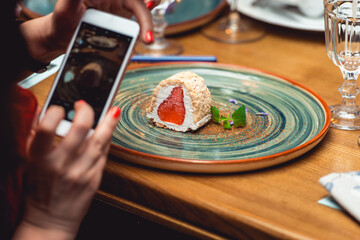 woman taking picture of a delicious creamy dessert with strawberry on a plate in the expensive restaurant. close view