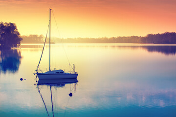 Little sailing boat reflects in  the serene water during sunrise. Masuria, Poland.