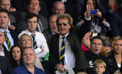 Celtic fan Rod Stewart reacts to a challenge on Adam Matthews from Motherwell's Keith Lasley during their Scottish Premier League soccer match at Celtic Park