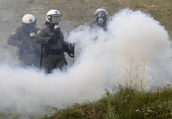 Riot policemen are seen through teargas during clashes at Keratea town near Athens