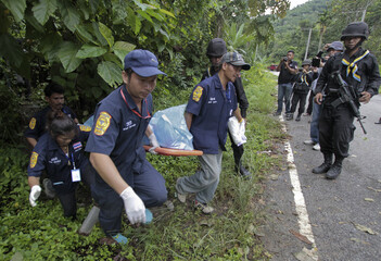 Rescue workers carry the body of a dead ranger after a bomb attack along a roadside in Yala province