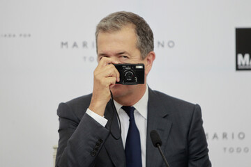Peruvian fashion photographer Mario Testino takes pictures during a news conference in Lima
