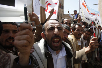 Yemeni public school teachers shout slogans during a protest to demand a pay rise, outside the parliament in Sanaa