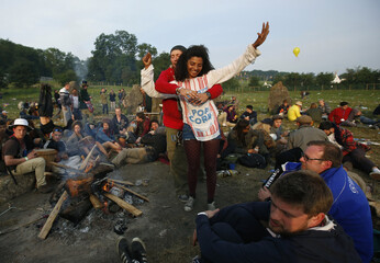 Festival goers dance at sunrise at the stone circle on the second day of Glastonbury music festival at Worthy Farm in Somerset