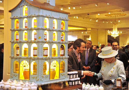 Britain's Queen Elizabeth is shown jars of honey by beekeeper Steve Benbow at the Fortnum and Mason store in central London