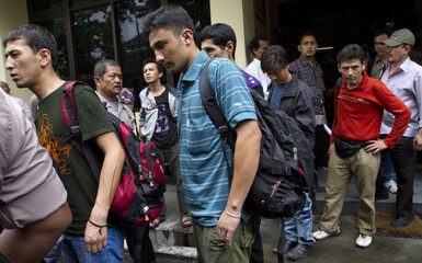 Illegal immigrants from Afghanistan, Iran and Iraq leave a police office in Bantul district
