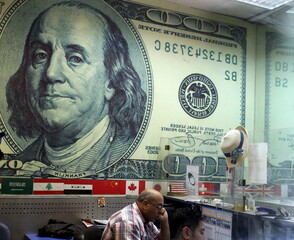 A mirror reflection shows an employee working in a foreign exchange office in central Cairo