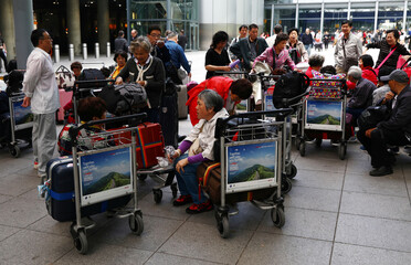 People wait with their luggage at Heathrow Terminal 5 in London