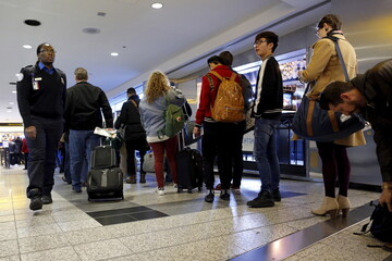 A Transportation Security Inspector (TSI) watches over travelers waiting in line at a security checkpoint at La Guardia Airport in New York