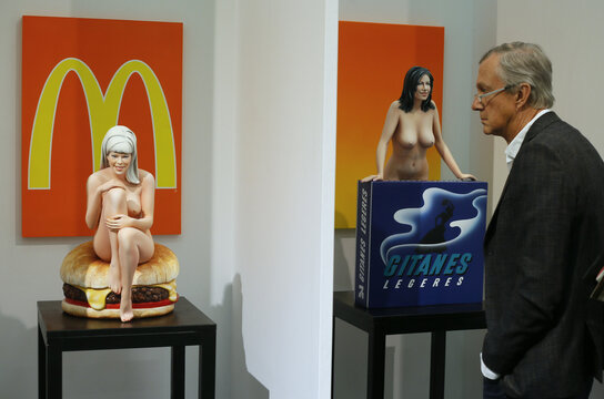 """A man looks at two sculptures of U.S. pop artist Mel Ramos at the """"Art Cologne"""" art fair in Cologne"""