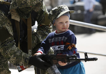 Pro-Russian armed man lends his weapon to a boy posing for a picture for his father in front of the seized town administration building in Kostyantynivka