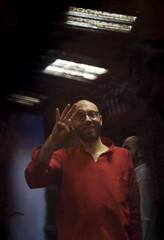 Former presidential office manager Ahmed Abdel-Ati, gestures with the Rabaa sign, symbolizing support for the Muslim Brotherhood, at a court in the outskirts of Cairo, Egypt