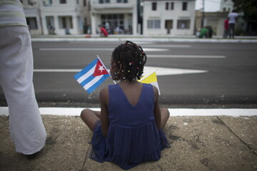 A child holds a Cuban and a Vatican flag as she waits for the arrival of Pope Francis from the airport in Havana