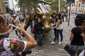 Chinese tourists pose for photographs with a landmark statue of a bull in New York