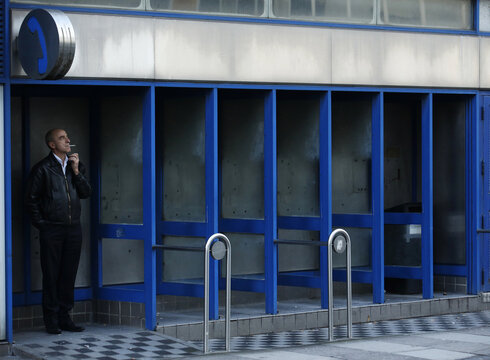 A man smokes in a row of empty telephone booths in London