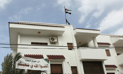 Syrian flags fly over the its embassy building in Tripoli