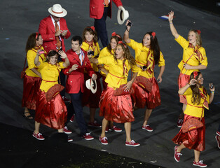Members of Spain's contingent wave as they participate in the athletes parade during the opening ceremony of the London 2012 Olympic Games at the Olympic Stadium