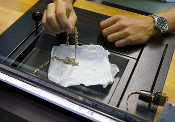 A cashier appraises a gold necklace left by a client in exchange for a loan at the Mont de Piete in central Brussels