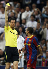 Referee Stark shows a yellow card to Barcelona's Keita during their Champions League semi-final first leg soccer match against Real Madrid in Madrid