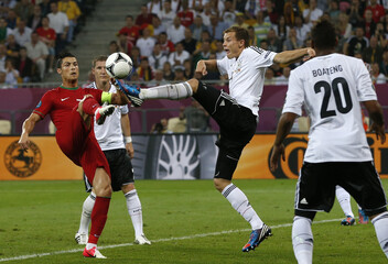 Portugal's Ronaldo fights for ball with the Germany's Badstuber during their Group B Euro 2012 soccer match at the New Lviv stadium in Lviv