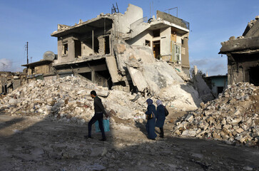 People walk on the rubble of damaged buildings in Azaz