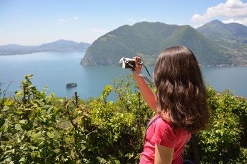 Beautiful girl take a photo with a mirrorless to the landscape of lake and mountains in sunny day. Travel healthy lifestyle concept.
