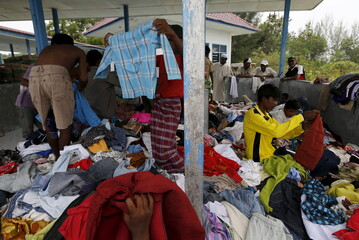 Rohingya migrants look for garments in a pile of donated clothes inside a temporary shelter in Kuala Langsa