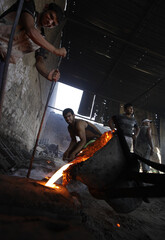 Iraqi workers pour molten iron taken from destroyed vehicles into a frame to be formed into sewage covers at a workshop in Baghdad
