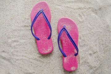 Pink sandal on sandy beach