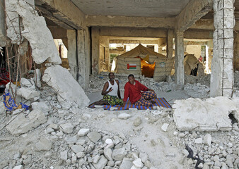 Men sit in a building destroyed during a fight between al Shabaab militants against African Union and Somali Government forces in Mogadishu