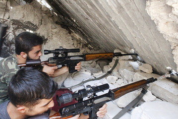 Free Syrian Army fighters aim their weapons as they take a defensive position in Aleppo's Karm al-Jabal district
