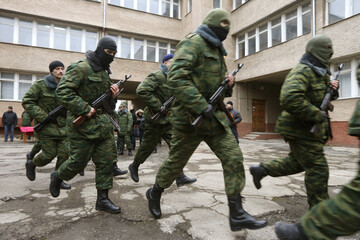 Members of a pro-Russian self defence unit run after swearing an oath to the Crimean government in Simferopol