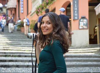 Beautiful young woman taking photo in Bellagio town, Como Lake, Italy