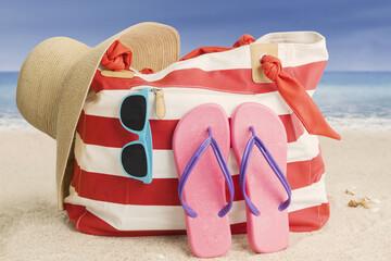 Woman bag and beach item on sand