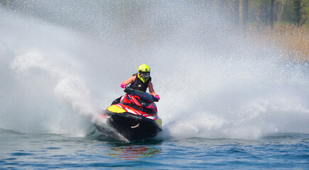 Jet Ski  racer cornering at speed creating at lot of spray.