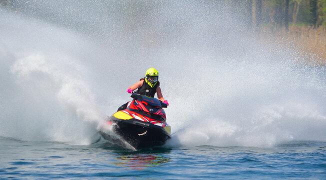 Jet Ski  racer cornering at speed creating at lot of spray.