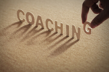 """The word """"coaching"""" wooden letters wooden on cork board background."""