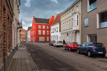 Empty Street In Old Town Bruges (Belgium),With Red Brick Buildings At Cloudy Day.Off-Season Realistic View With Medieval Color Traditional Houses And Several Cars.Street In Historic Centre Of Bruges