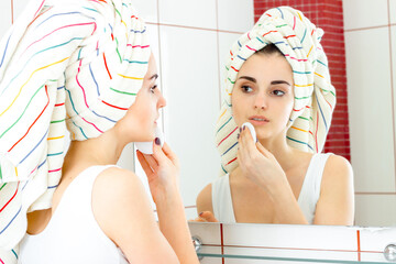 young beautiful girl with towel on head washes away make-up