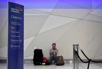 A woman waits with her luggage at Gatwick Airport in southern England