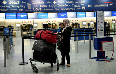 A woman and child wait with their luggage at Gatwick Airport in southern England