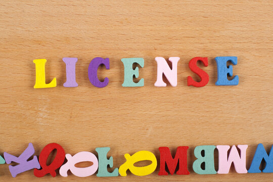 LICENSE word on wooden background composed from colorful abc alphabet block wooden letters, copy space for ad text. Learning english concept.